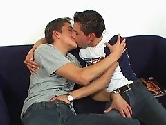 Turned on gay boys give each other a good handjob on sofa