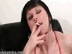 Mina lights up a cigarette and fucks her dildo