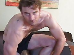 Sexy man is beating his meat sitting on the leather sofa